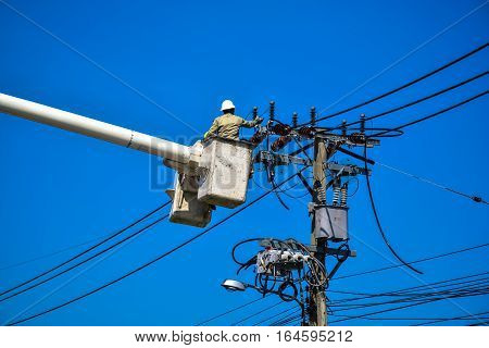 Electrician lineman repairing work on electric post power pole