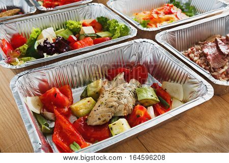 Healthy eating, diet concept. Take away organic food. Weight loss nutrition in foil boxes. Vegetable salads, steamed beef on white wood