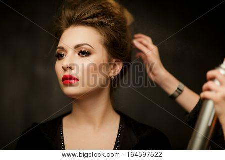 Stylist corrects hair of beautiful brunette in studio