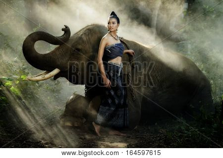 Beautiful asian woman and elephant with Thai culture traditional dress