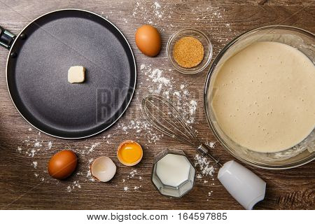 Frying pan with oil, bowl with dough for pancakes on brown table