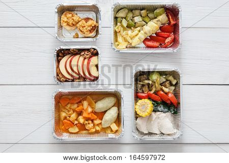Healthy restaurant food background. Eating right concept. Fresh diet daily meals delivery. Fitness nutrition, vegetables, meat and fruits in foil boxes. Top view, flat lay on wood