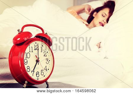 Sleeping Woman With Her Hand Touching Alarm Clock On Bed