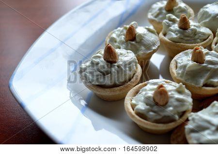 Little bites of hazelnut pintxos in a simple blue-striped dish