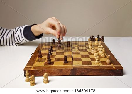 Child's hand holding chess figure while playing chess. Close up. Education, game, lifestyle concept.