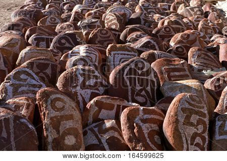 Pebbles from sacred Lake Manasarovar with hieroglyphs and main  Buddhist mantra
