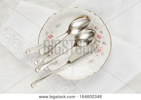 Top view of the beautiful table setting with white plate lacy linen napkin and cutlery