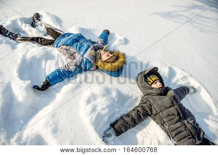 Brothers having fun playing in the snow in winter. Two brothers make angels in the snow.