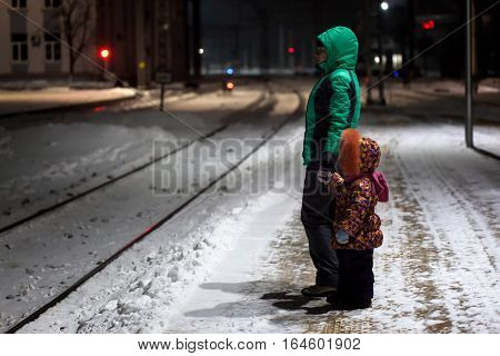 Young woman with child waiting for a train at small railway station at winter night