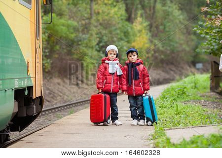 Two Boys On A Railway Station, Waiting For The Train With Suitcase