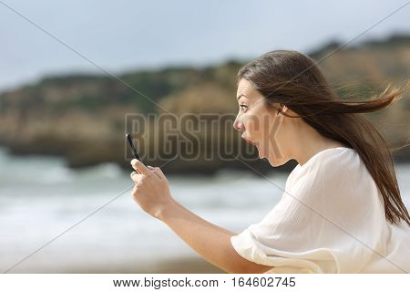 Side view of an humorous amazed girl with her smart phone with the wind moving her hair on the beach
