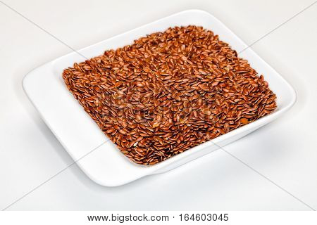 Flax, Flaxseeds. Flaxseed, in a white container. White background. One hundred grams of ground flaxseed supplies about 534 calories, 41 grams of fat, 28 grams of fiber, and 20 grams of protein. Image taken with macro lens.