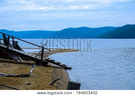 Pier With A Ladder To The Water. View On Lake Baikal And Beautiful Sky With Clouds. Siberia, Russia.