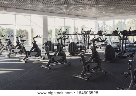 Modern gym interior with equipment. Fitness club with training exercise bikes, backlight.