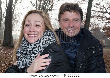 A Middle-aged Couple Walks In The Woods During The Autumn When Well Winter