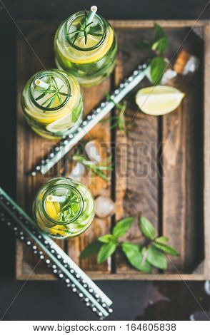 Citrus and herbs infused sassi water for healthy eating, dieting in glass bottles in wooden tray over dark background, selective focus, top view, copy space. Clean eating, healthy lifestyle concept