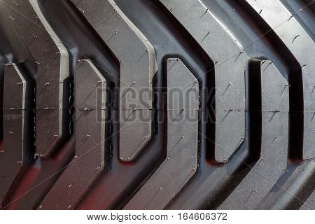 Detail of heavy tractor wheel and tire. Tread close up