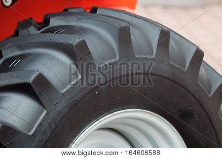 A fragment of a huge wheel and tire of construction equipment