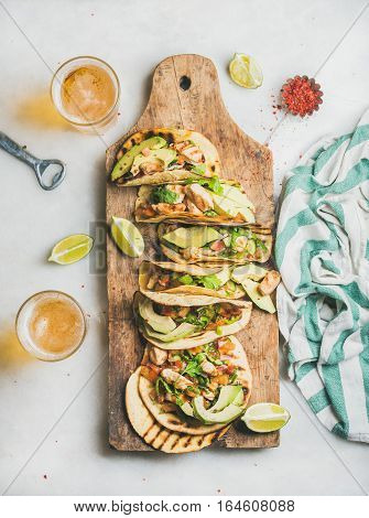 Healthy corn tortillas with grilled chicken, avocado, fresh salsa, limes on wooden board and beer in glasses over light grey marble table background, top view. Gluten-free, allergy-friendly concept