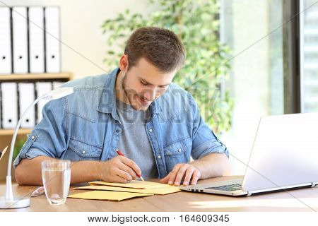 Entrepreneur writing address in a padded envelope before to send it