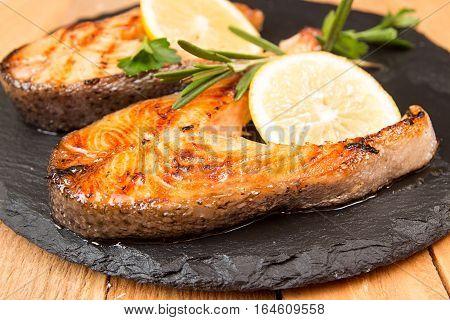 Grilled Trout Fillet Garnish Lemon On Black Slate