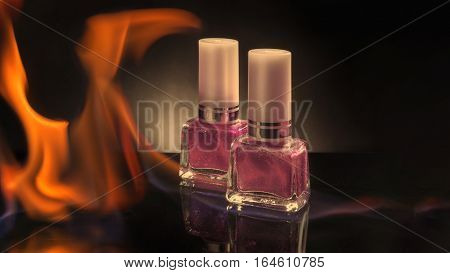 Two bottles of colored nail polish on a black background burning in a flame of fire