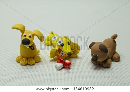 Toys of three dogs from plasticine and a bone tied up by a band on a light background