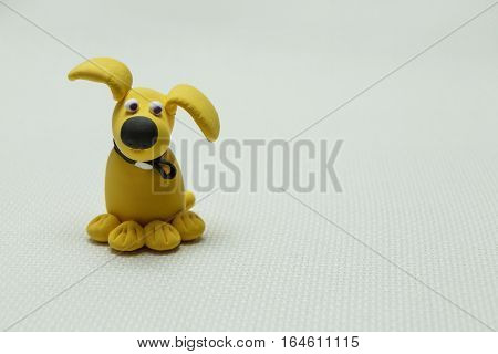 Toy of a dog from plasticine on a light background