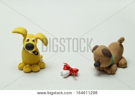 Toys of two dogs from plasticine and a bone tied up by a band on a light background