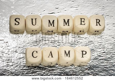 Summer camp text on a wooden cubes on a shiny silver background