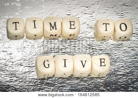 Time To Give Text On A Wooden Cubes On A Shiny Silver Background
