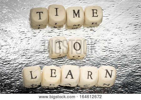 Time To Learn Text On A Wooden Cubes On A Shiny Silver Background