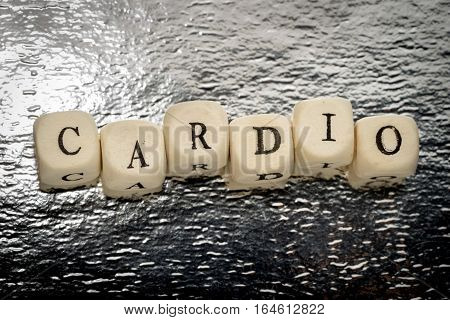 Cardio word (letters unevenly) on a wooden cubes on a shiny silver background