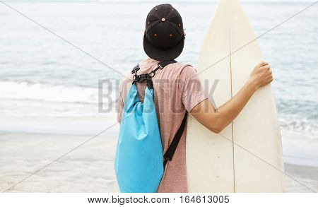 Hobby, Leisure And Summer Vacations. Back Shot Of Stylish Young Surfer Wearing Snapback And Backpack