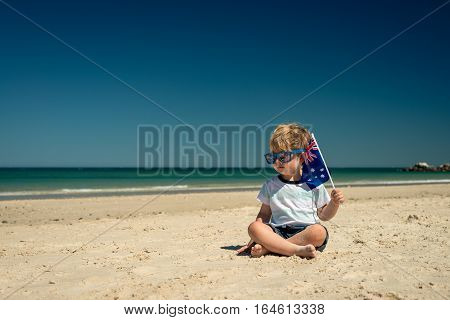Cute smiling kid with flags of Australia sitting on the sand at the beach