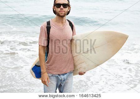 Summer Vacations, Active Lifestyle And Leisure Concept. Outdoor Portrait Of Young Surfer In Black Sh