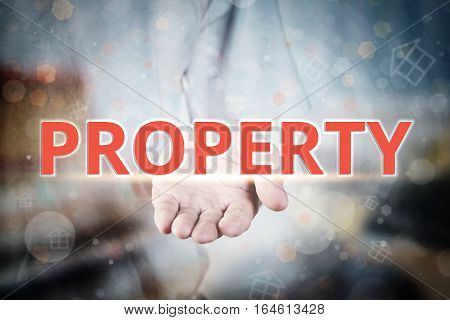 Man Hand Holding Property Text On Blurry Home Icon Property Background.