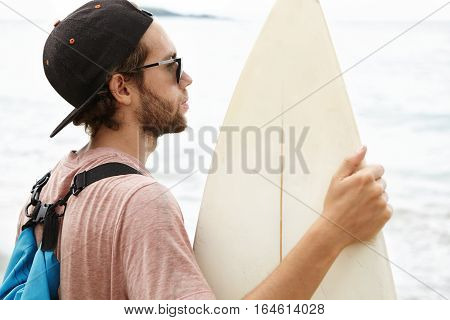 Close Up Shot Of Young Surfer With Stylish Beard Wearing Backpack And Baseball Cap Holding White Sur