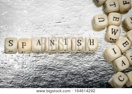 Spanish Word On A Wooden Cubes On A Shiny Silver Background With Heap Of Letters