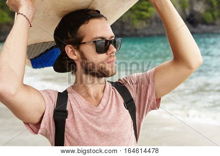 Hobby And Vacation. Handsome Young Man With Beard Wearing Stylish Sunglasses And Snapback Holding Su