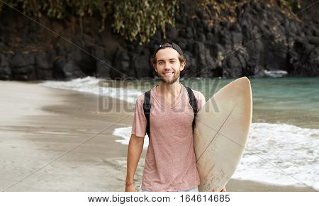 Summer Vacation, People, Travel And Watersports Concept. Smiling Young Man With Surfboard Walking Do