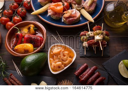 Top view of variety of mediterranean starters - spanish tapas with chorizo prawns and olives