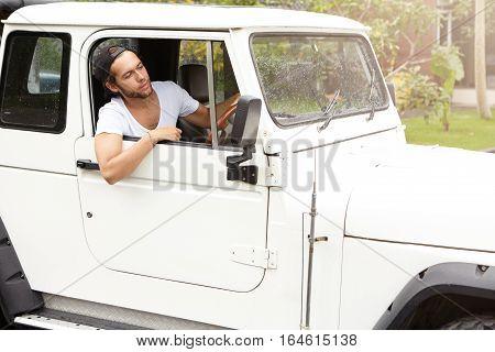 Stylish Caucasian Traveler Having Break During Safari Adventure Trip. Young Bearded Hipster Man In W