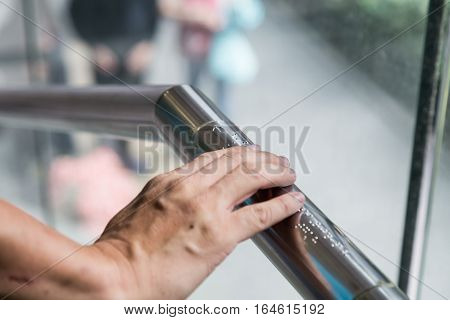 Hand reading Braille inscriptions for the blind on public amenity railing