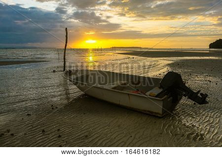 Beautiful seascape sunrise scenery with golden sun at horizon and traditional fisherman boat during low tide in Labuan,Federal Territory of Labuan,Malaysia.