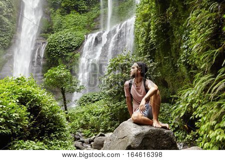 Nature, Tourism And People. Young Barefooted Tourist Wearing Jeans Short And Backpack Sitting On Big