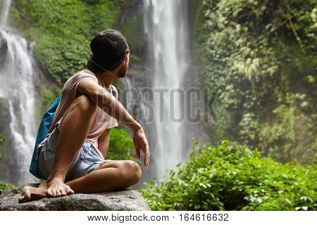 People, Lifestyle And Adventure Concept. Stylish Young Man Wearing Cap Backwards Sitting On Big Rock