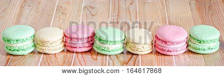 Colored Sweet Macaroons, French Traditional, Cream,  White Plate, Close Up, Wood Background
