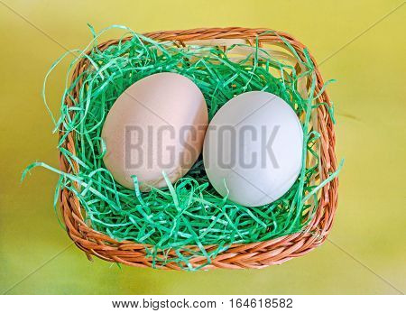 Light Green Duck Egg And Light Brown Chicken Egg, Brown Basket With Grass, Yellow Background.