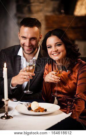 Happy couple tasting delicious dessert in restaurant